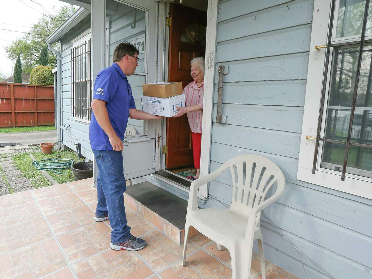 Geoff Newby gives Lucy Hernandez a delivery of emergency food due to the Covid-19 outbreak Monday, March 16, 2020, in Houston. Operation IMpact usually occurs in May or June (for hurricane season), but Interfaith Ministries will be making the deliveries in March due to the COVID-19 outbreak. All of its 4,300+ seniors received the emergency food this month, in case the virus impacts Meals on Wheels deliveries.