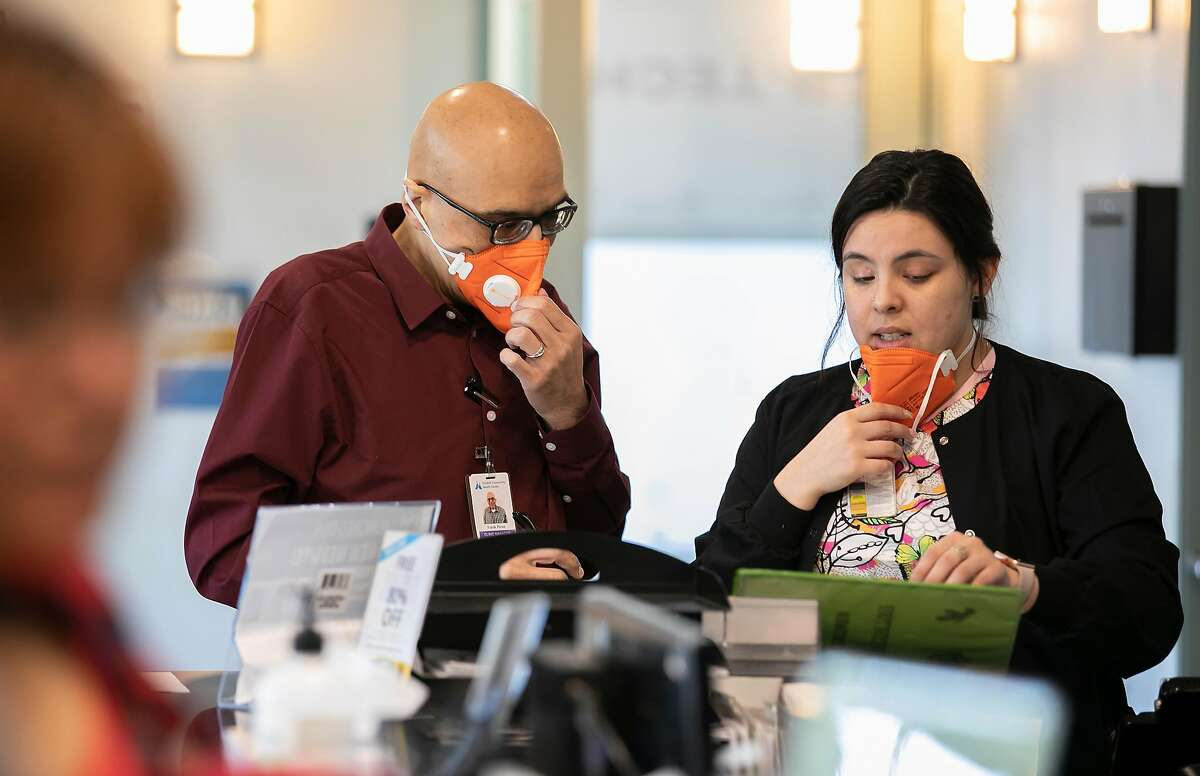 Wearing N95 face masks, from left to right, Clinic Manager Frank Perez and Back Medical Assistant Ericka Salcido confer at the front desk of the Foothill Community Health Center on Monday, Feb. 10, 2020 in San Jose, Calif.