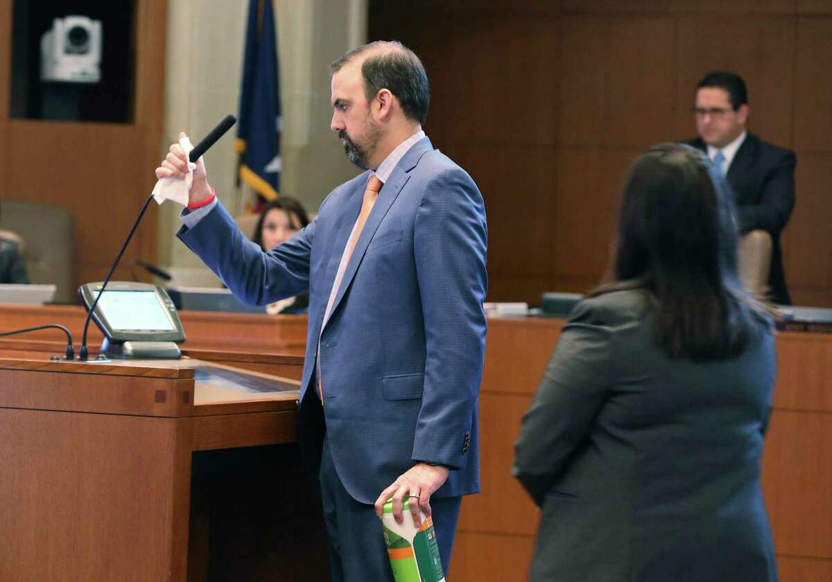 John Peterek, assistant to the city manager, wipes down the microphone and lectern.