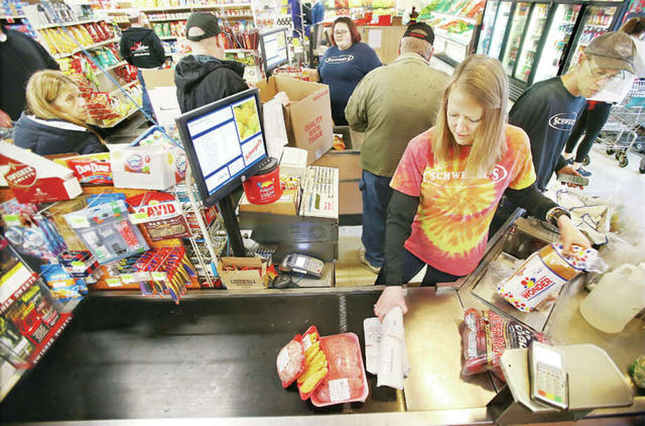 Checkers, like manager Monica Schwegel, right, are doing their best to keep food moving at Schwegel's Market at the corner of Alby and 9th streets in Alton while coping with the demand caused by COVID-19 virus concerns. Most items are in stock at the store, including fresh meats in the deli section of the store.