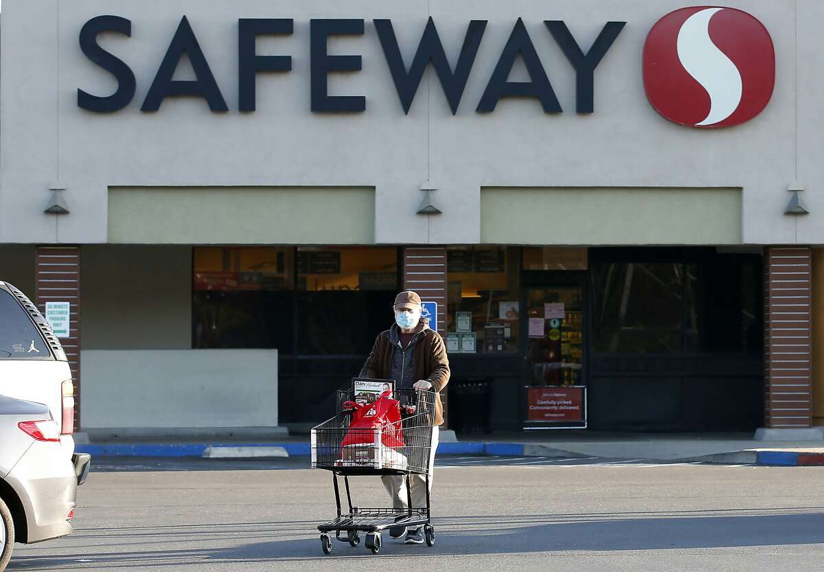Wearing a mask for protection against the coronavirus, Henry Powell, heads to his car after shopping at a Safeway store in Sacramento, Calif., Thursday, March 19, 2020. Safeway is among the stores that are offering special shopping hours for seniors, like Powell, who is in his 70's, to get their groceries before opening to the rest of the public. (AP Photo/Rich Pedroncelli)