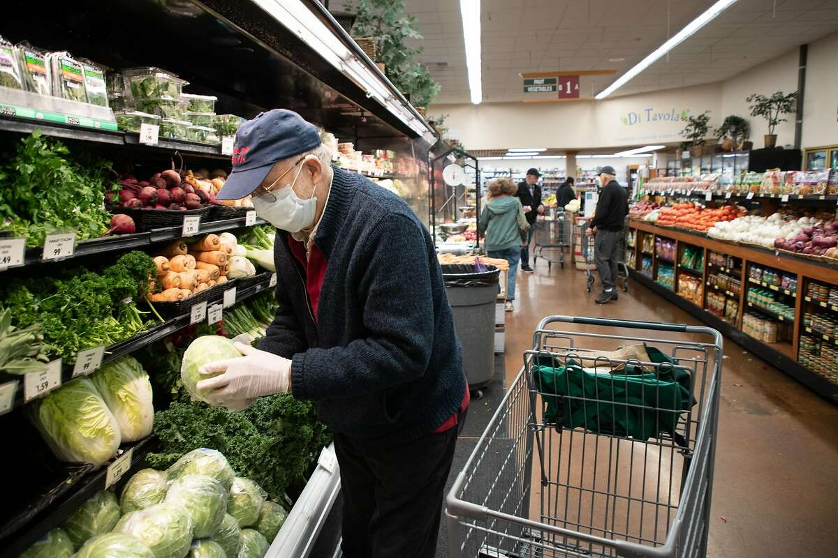 Rene Azigdor, 85, of San Jose, picks up a head of cabbage as he shops at Zanotto's Willow Glen Market Thursday, March 19, 2020, in San Jose, Calif. The store is open only to seniors from 8 - 9 a.m.
