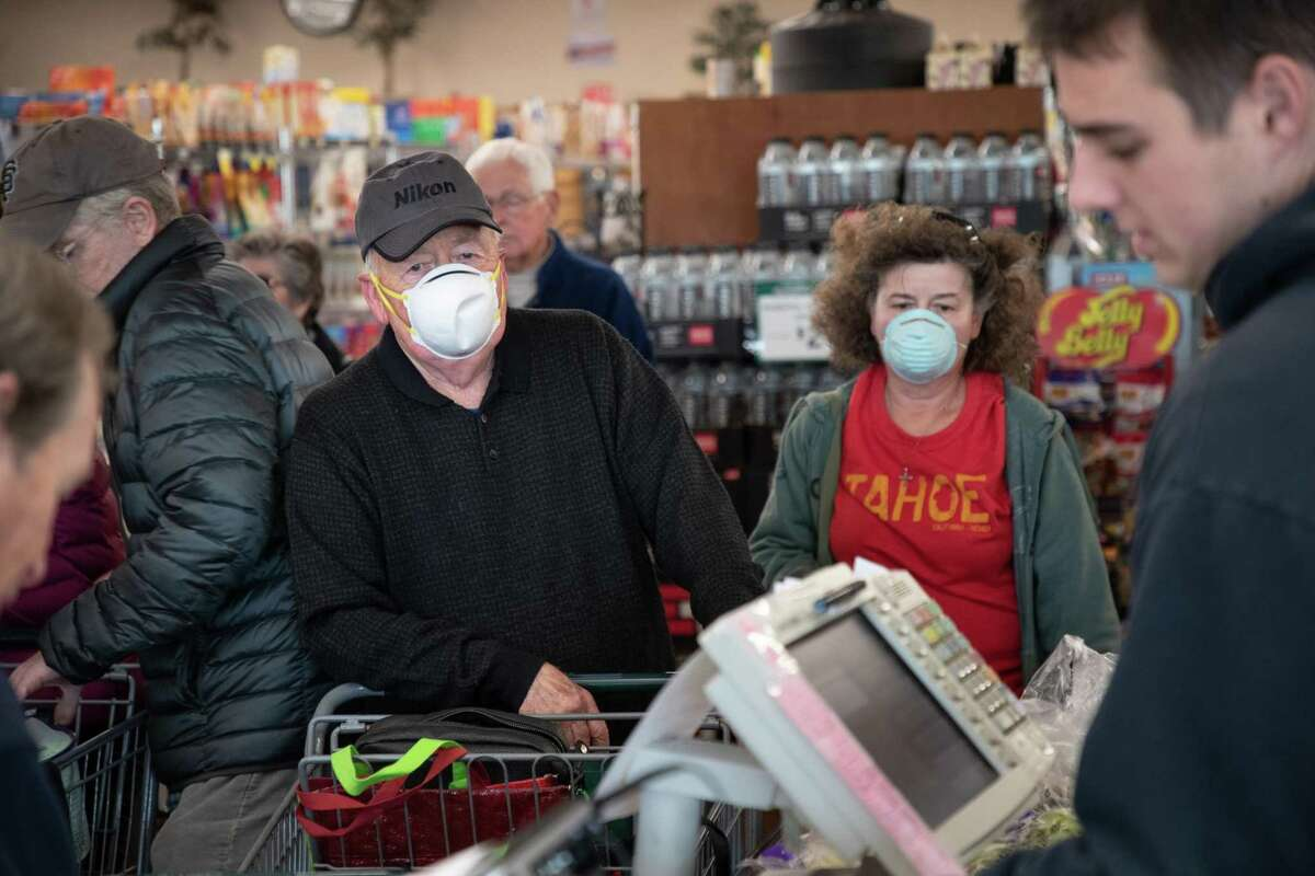 Robert Cushing, 78, and his daughter, Michele Cushing, wait in the checkout line as seniors shop at Zanotto's Willow Glen Market Thursday, March 19, 2020, in San Jose, Calif. San Jose became the latest Bay Area city in requiring large grocery stores to offer hazard pay to its employees.