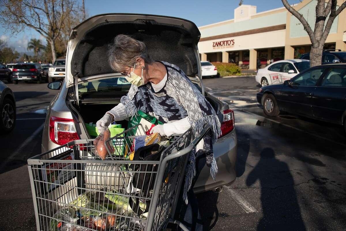 Faye Kimura, of San Jose, loads up her car after shopping at Zanotto's Willow Glen Market Thursday, March 19, 2020, in San Jose, Calif. The store is open only to seniors from 8 - 9 a.m.