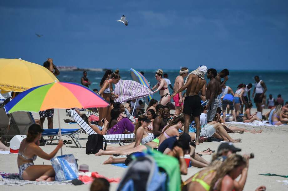 Tourists enjoy the water in Miami Beach, Florida, on March 18, 2020. They crowded the beaches, filled discos and sweated together at dances, ignoring for days the recommendations to keep their distance. Photo: CHANDAN KHANNA/AFP Via Getty Images