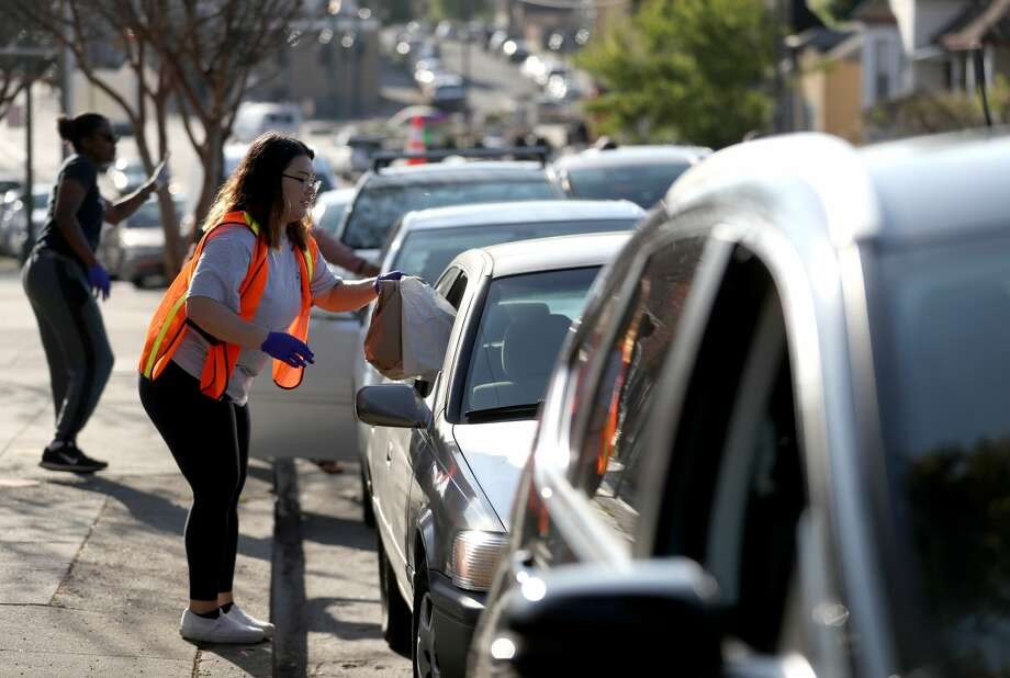 A member of the faculty at a California elementary school passes out food to families of students in Oakland, California. Photo: Justin Sullivan/Getty Images / 2020 Getty Images