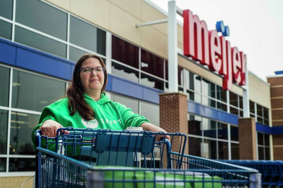 Tracey Allen of Midland, a part-time shopper with Shipt, poses for a portrait as she takes a quick break between fulfilling orders Thursday, March 19, 2020 at Meijer in Midland. Allen had already delivered four orders by 11 a.m. (Katy Kildee/kkildee@mdn.net)