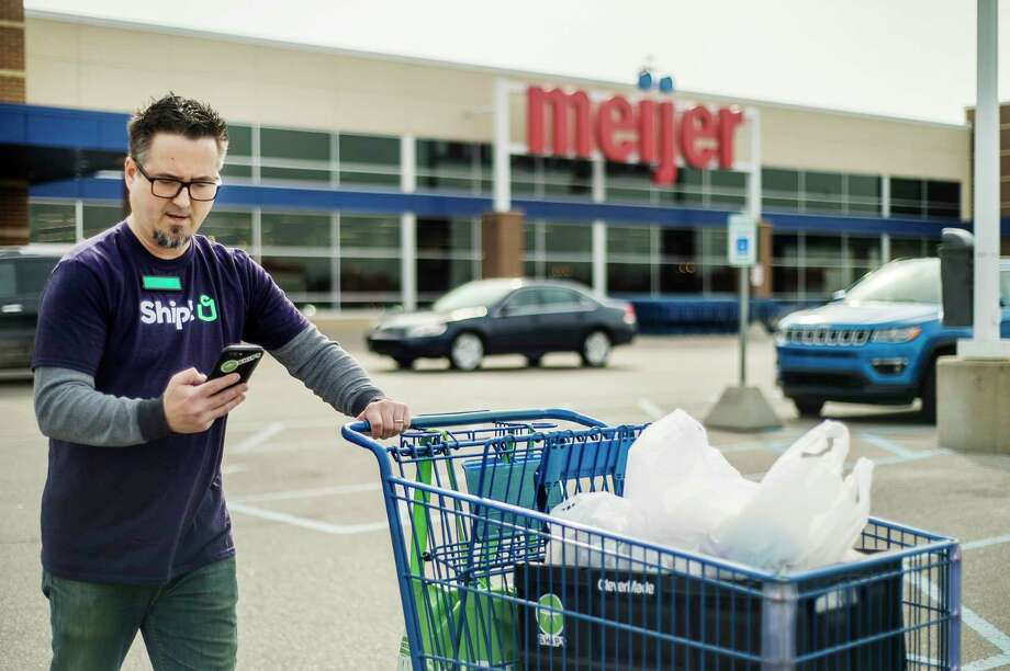Shipt shopper Greydon Koellmann transports an order to his vehicle while texting with a customer Thursday morning at Meijer in Midland. For more photos, go to www.ourmidland.com. (Katy Kildee/kkildee@mdn.net)