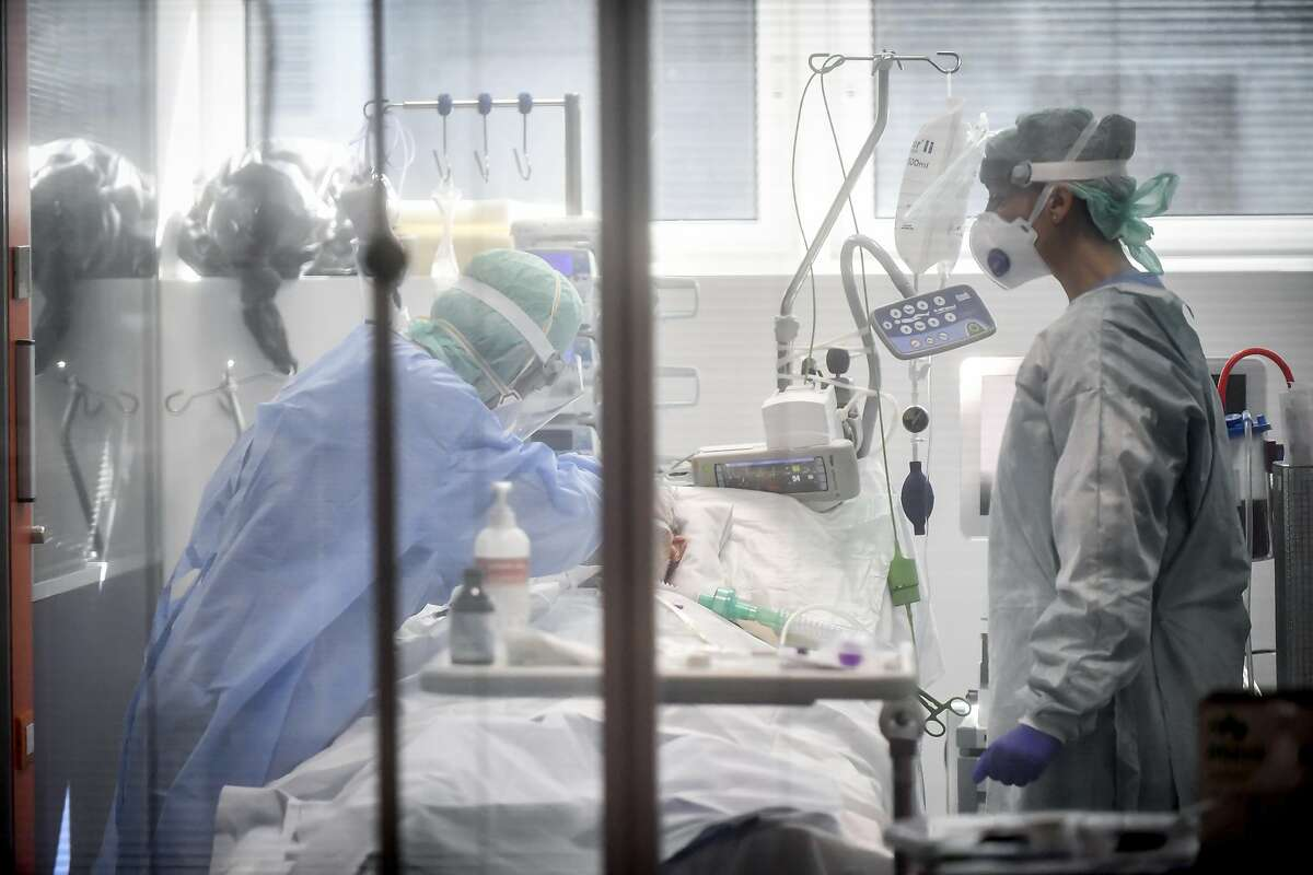 Medical personnel at work in the intensive care unit of the hospital of Brescia, Italy, Thursday, March 19, 2020. Italy has become the country with the most coronavirus-related deaths, surpassing China by registering 3,405 dead. Italy reached the gruesome milestone on the same day the epicenter of the pandemic, Wuhan, China, recorded no new infections. For most people, the new coronavirus causes only mild or moderate symptoms. For some it can cause more severe illness. (Claudio Furlan/LaPresse via AP)