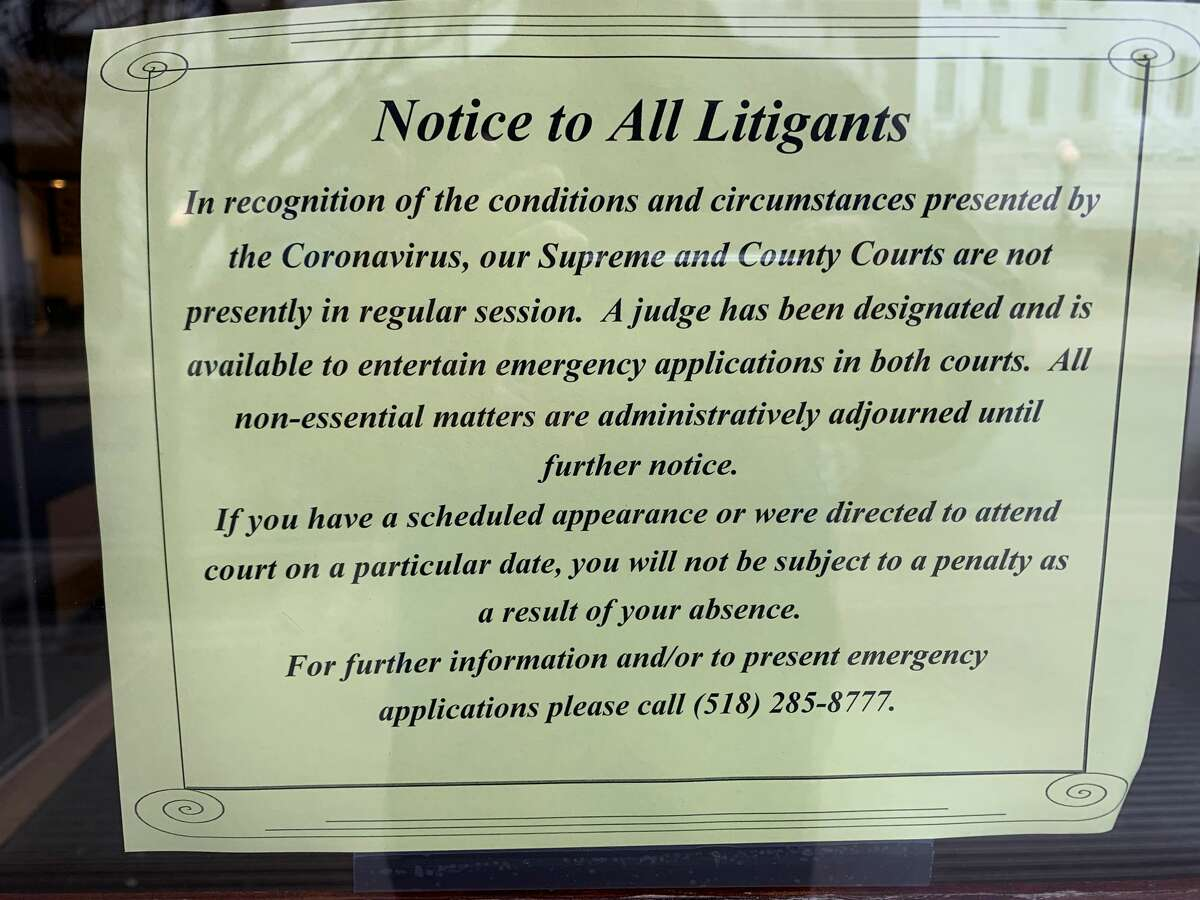 """Sign notifies litigants that state Supreme Court and Albany County Court are """"not presently in session."""" The website of the state's Unified Court System says court is being held at the Court of Claims."""