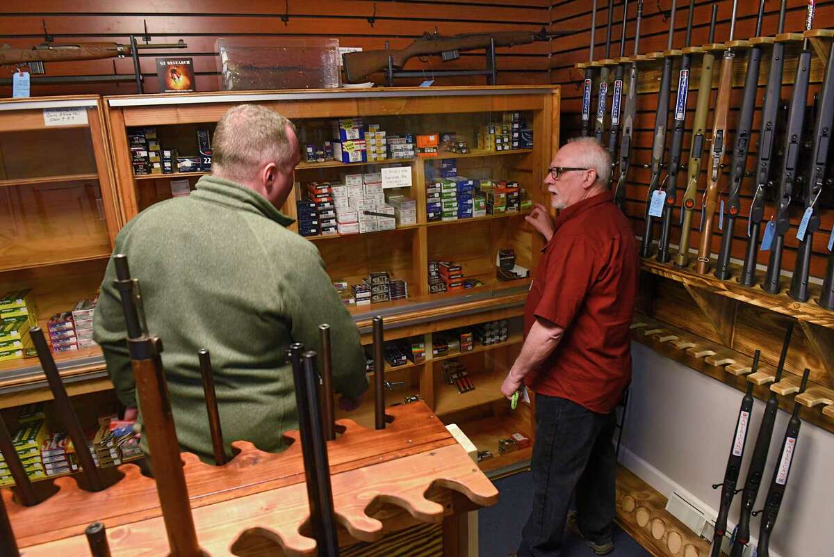 Employee Jim Retajczyk, right, retrieves ammunition for James of Latham (he didn't want to give his last name) a customer at Upstate Guns & Ammo store on Thursday, March 19, 2020 in Schenectady N.Y. (Lori Van Buren/Times Union)