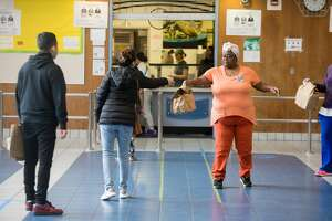 Oakland School District Cafeteria employee Michelle Franklin hands out donated meals from Revolution Foods and Steph and Ayesha Curry. Cafeteria staff and volunteers handed out grab and go meals to Oakland students and families in the Oakland High School cafeteria on March 19th, 2020. Schools in the district are closed due to shelter-in-place orders due to the the COVID-19 coronavirus.