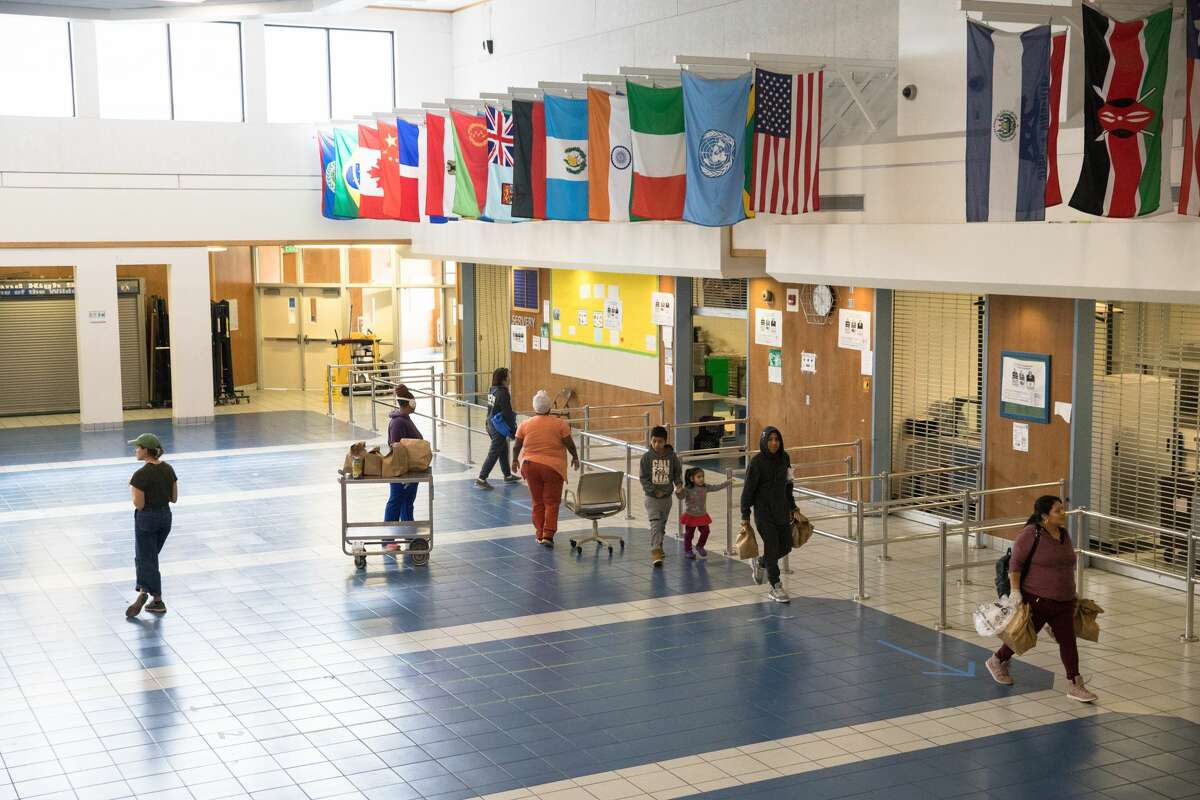 FILE - Oakland students and families carry out grab and go meals prepared by the cafeteria staff in the Oakland High School cafeteria on March 19th, 2020. Schools in the district are closed due to shelter-in-place orders due to the the COVID-19 coronavirus.