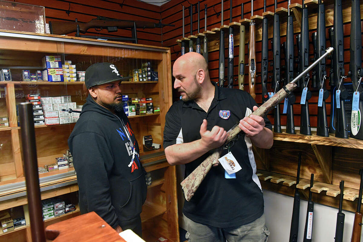 Craig Serafini, owner of Upstate Guns & Ammo, right, shows Kevin Atchana how to use the bolt action rifle that his is thinking of buying at Serafini's gun store on Thursday, March 19, 2020 in Schenectady, N.Y. (Lori Van Buren/Times Union)