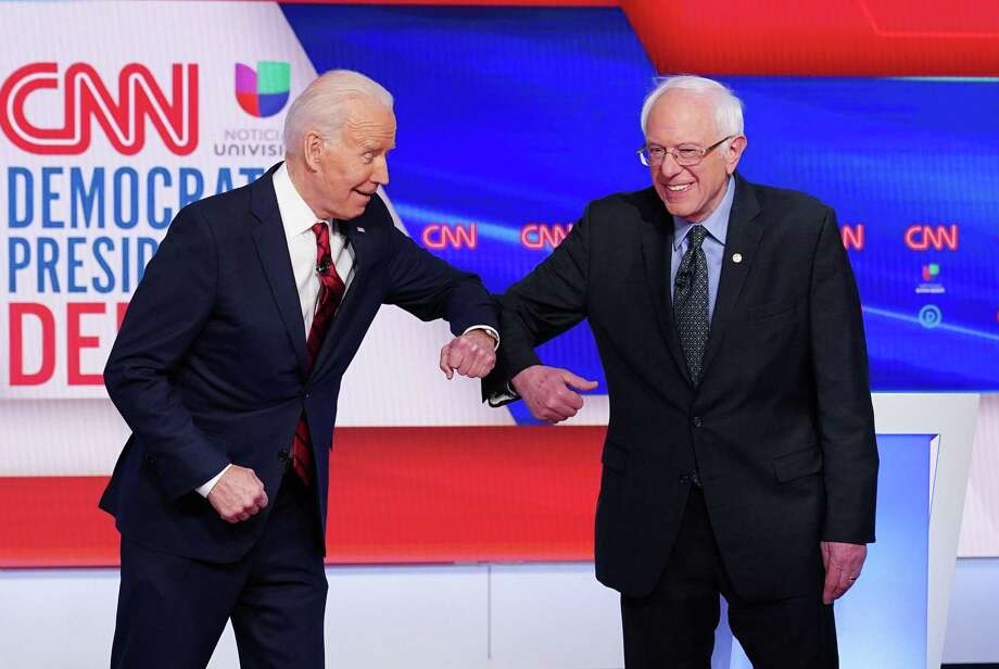 Democratic presidential hopefuls former U.S. vice president Joe Biden (L) and Sen. Bernie Sanders (R) greet each other with an elbow bump as they arrive for the 11th Democratic Party 2020 presidential debate in a CNN Washington Bureau studio in Washington, D.C. on March 15. The handshake is going our of style, and it's a good thing. Photo: MANDEL NGAN /AFP Via Getty Images / AFP or licensors