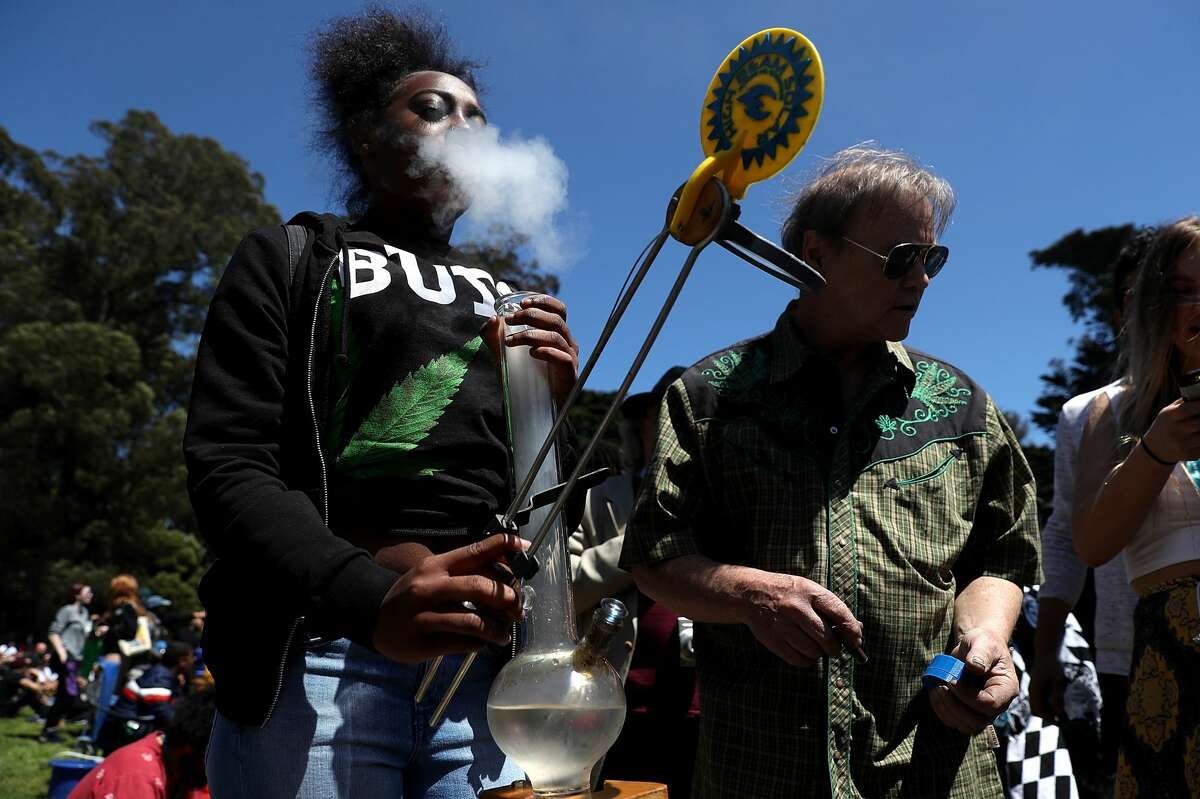 A man blows smoke after taking a hit from a bong during a 4/20 celebration on Hippie Hill in Golden Gate Park on April 20, 2018 in San Francisco, the first year of legal recreational consumption.