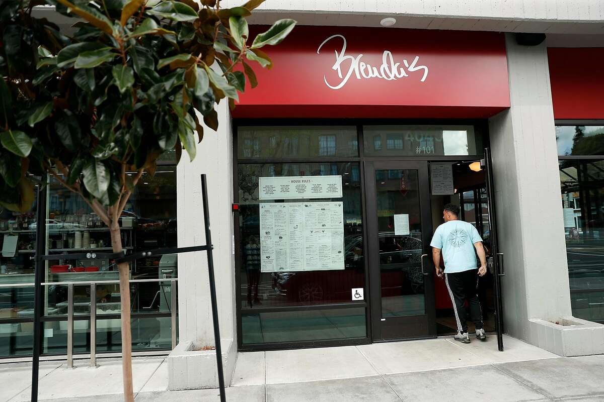 A customer enters Brenda's to pick up an order in Oakland, Calif., on Wednesday, March 19, 2020.