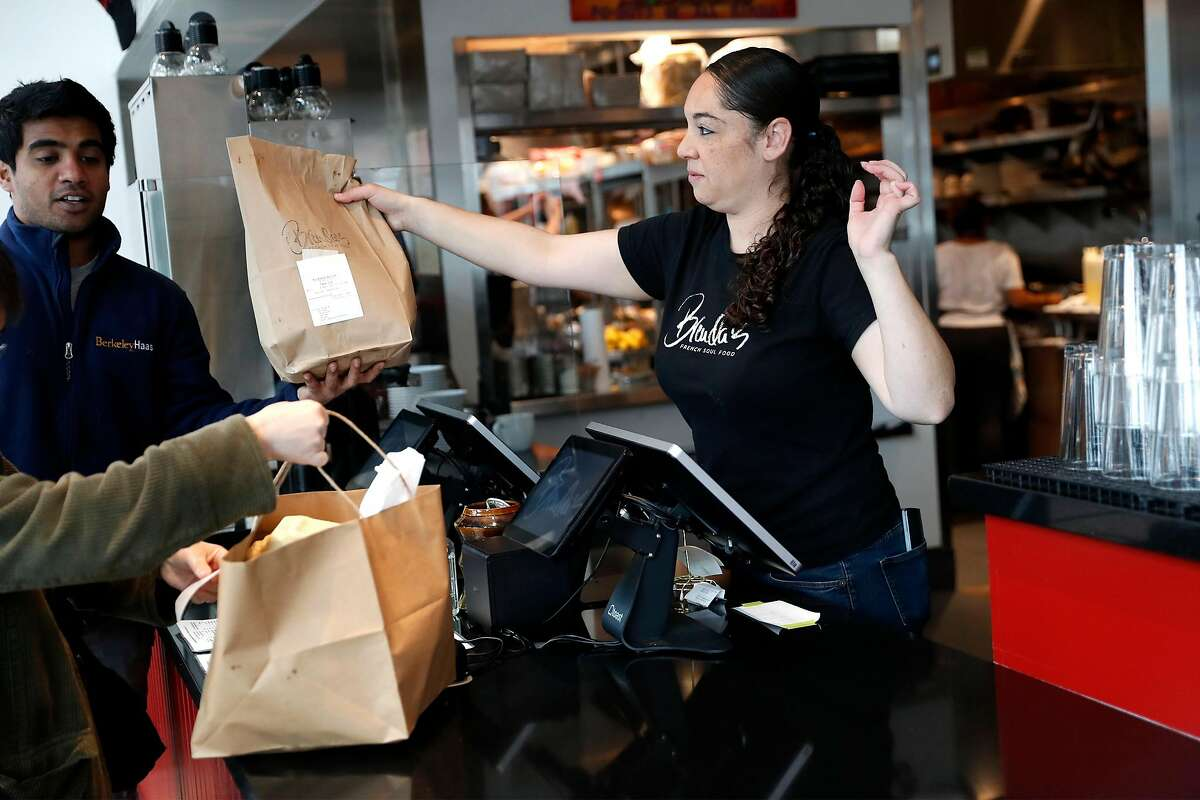 Tracey Anderson hands take out orders to customers while working at Brenda's in Oakland, Calif., on Wednesday, March 19, 2020.