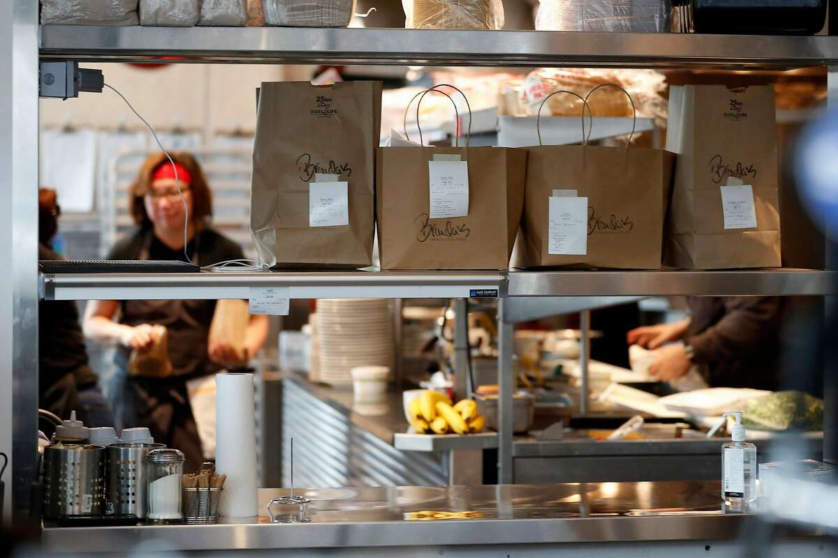 Owner Brenda Buenviaje works in the kitchen behind a shelf full of take out orders at Brenda's in Oakland, Calif., on Wednesday, March 19, 2020.