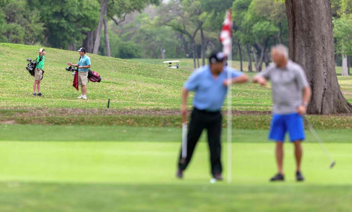 A pair of golfers, left, walk the Brackenridge Park golf course on March 18 as two others give an elbow high five to each other after making a putt. The governor ordered golf courses to close as non-essential businesses but state officials are interpreting the order as allowing walkers to play, with a minimum of course employees.
