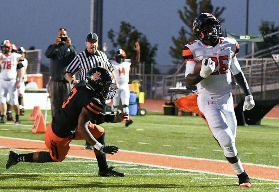 Edwardsville's Justin Johnson Jr. (26) runs in for a touched and out of reach of DeKalb's Cameron Grays (3) in action last season at the District 7 Sports Complex