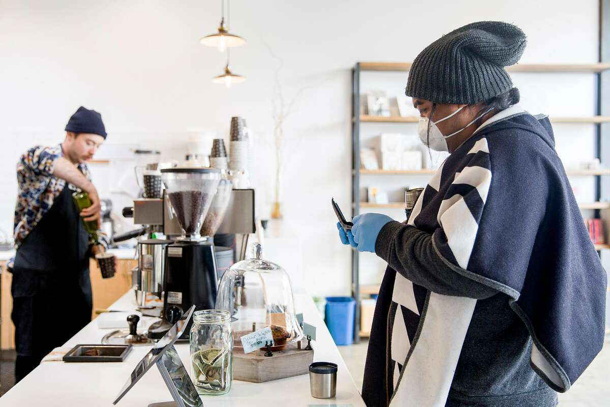 Po Savea of San Francisco wears a mask and gloves while ordering coffee from the Andytown Roastery in San Francisco, Calif. Wednesday, March 18, 2020. Production of online and grocery orders of coffee from Andytown has been placed in overdrive as they work to fill orders as well as keep both shops open for limited hours.