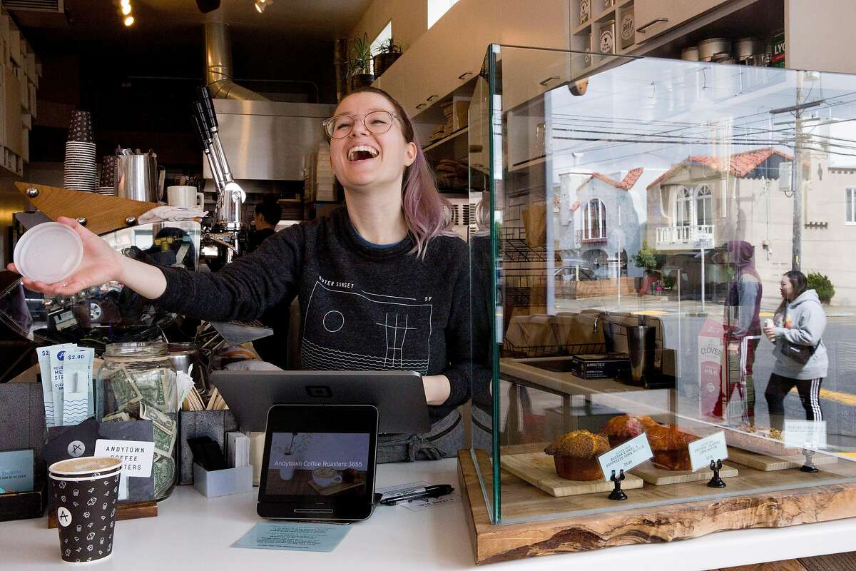 Jackie Szymborski calls out an order to customers waiting outside at the Andytown Lawton Street location in San Francisco, Calif. Wednesday, March 18, 2020. Andytown's shops have remained opened for to-go orders, but only two customers are allowed inside at one time to promote social distancing.