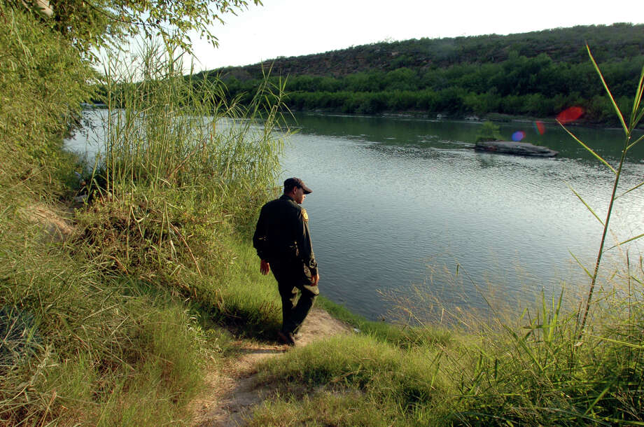 US Border Patrol agent David Borges surveys the banks of the Rio Grande as a bluff on the Mexican side makes it easier for the illegals to get a better view of the agents patrolling the area near Rio Bravo, Texas. Photo: Delcia Lopez/San Antonio Express News