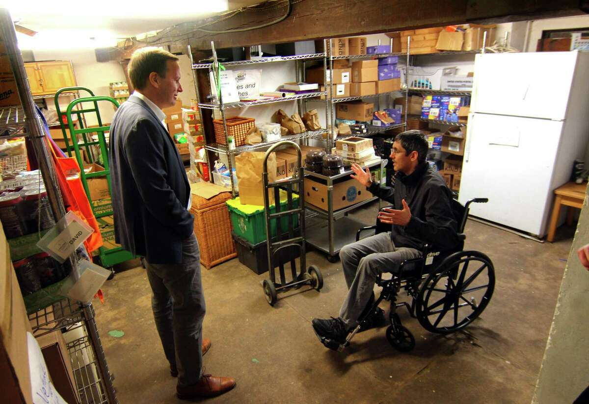 U.S. Sen. Chris Murphy listens to the concerns of Loaves and Fishes Pantry Executive Director James Cramer during a visit in New Haven Thursday.