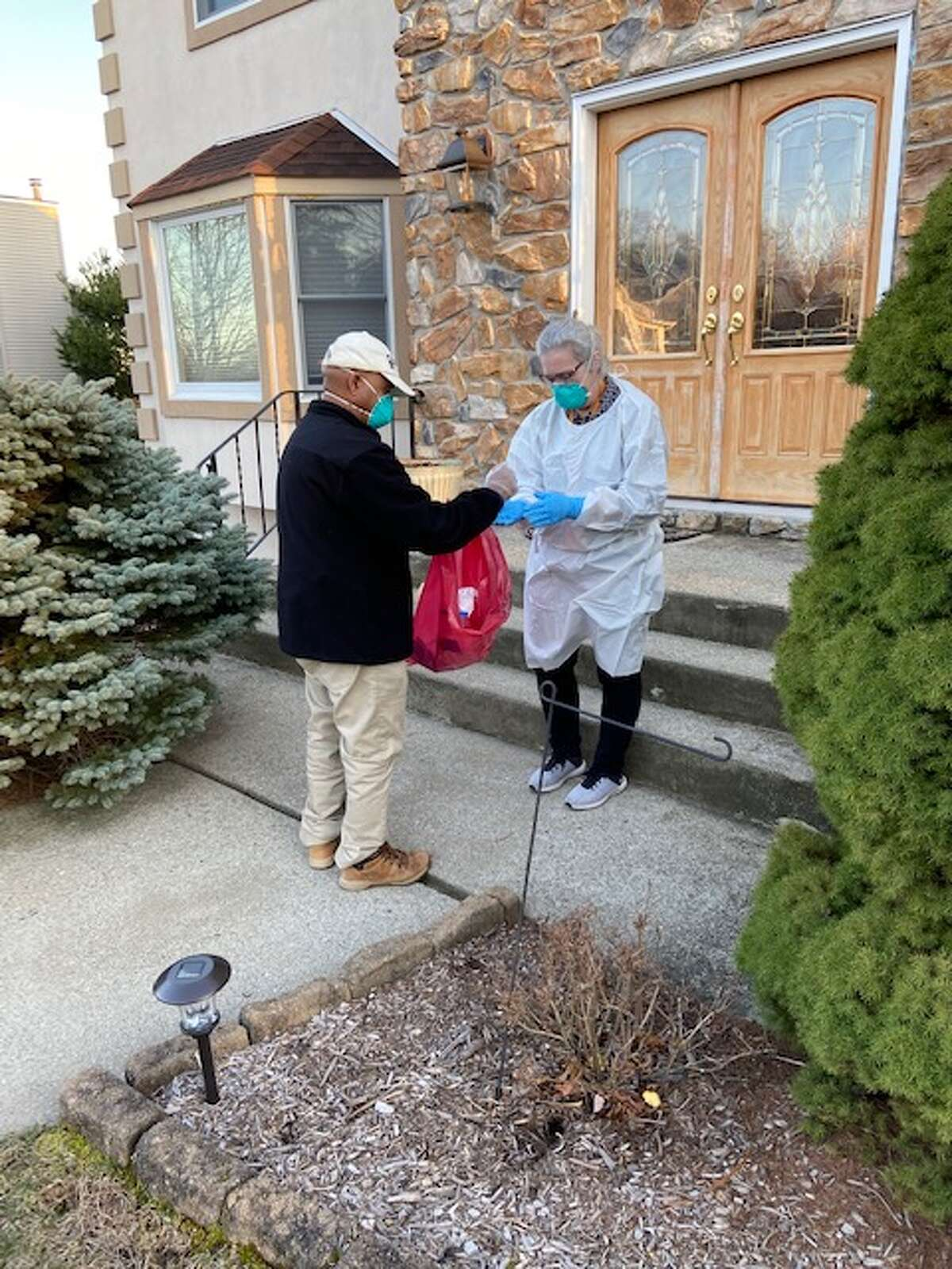 A state public health nurse wearing protective clothing and a state parole officer who was serving as her driver collect samples from residents in Westchester County last weekend. (Provided Photo)