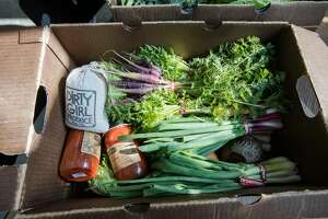 A CSA pre-packed box of fresh organic produce and shelf-stable pantry items from Dirty Girl Produce waiting to be picked up at Nari restaurant in Japantown in San Francisco, California on March 19, 2020.