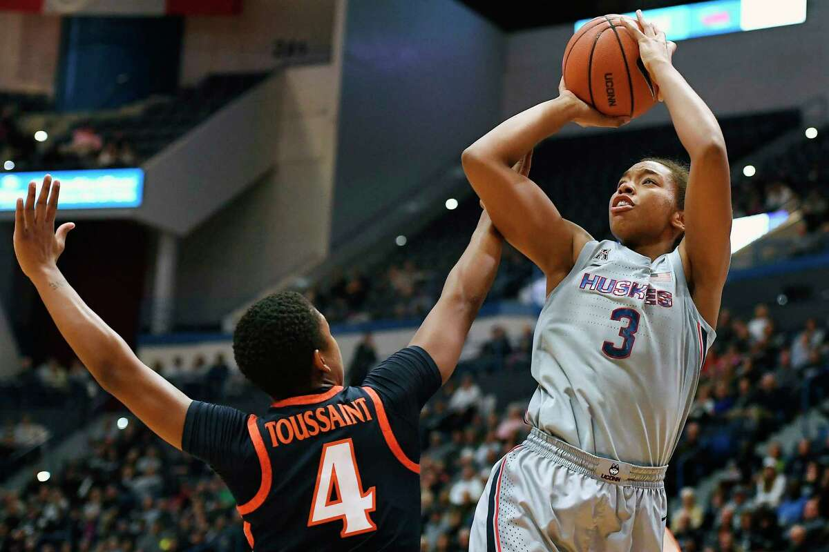 FILE - In this Nov. 19, 2019, file photo, Connecticut's Megan Walker (3) shoots over Virginia's Dominique Toussaint during the first half of an NCAA college basketball game in Hartford, Conn. Walker was selected to The Associated Press women's All-America first team, Thursday, March 19, 2020. Walker, who declared she was entering the WNBA draft and not returning for her senior season, averaged 19.7 points, 8.4 rebounds and 47.7% from the field. (AP Photo/Jessica Hill, File)