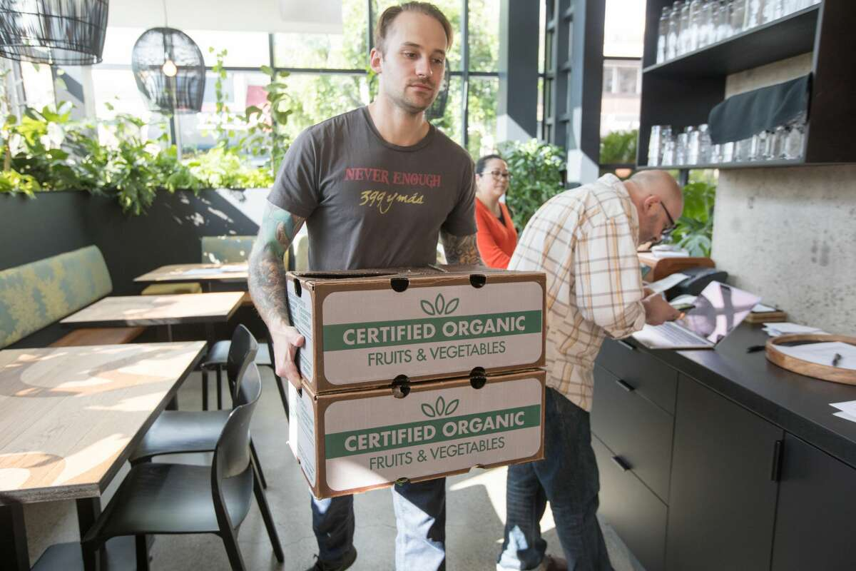 Max Alexander from Nari restaurant carries pre-packed boxes of CSA fresh organic produce from Dirty Girl Produce. The CSA boxes are waiting to be picked up at Nari restaurant in Japantown in San Francisco, California on March 19, 2020.