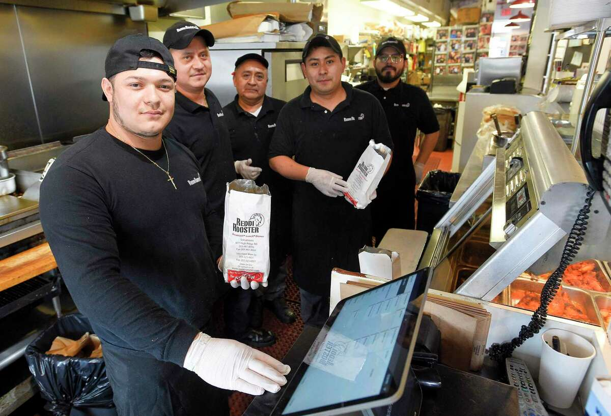 The serving staff of Reddi Rooster take out wear protective gloves on March 19, 2020 in Stamford, Connecticut.