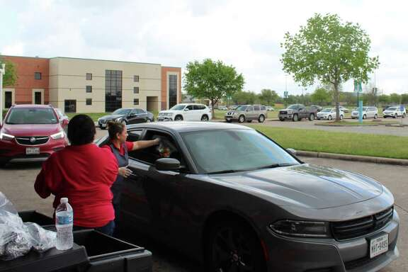 (left to right) Sandra Mejia and Erika Sacedo of Pasadena ISD's child nutrition services, hand out meals to families during the COVID-19 crisis-related school closure.