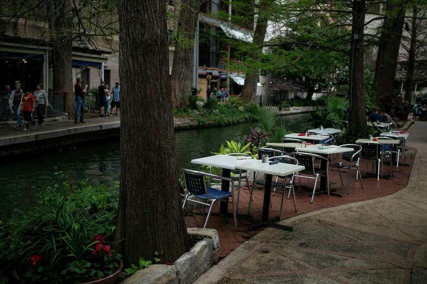 Empty tables line the river outside the County Line restaurant. The River Walk has become a much quieter place these days.