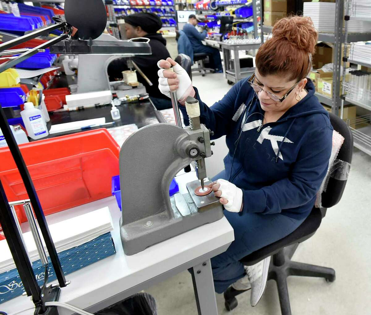 Esther Madera of Bio-Med Devices of Guilford, a mechanical assembler, works on an air-oxygen blender part Thursday at the plant.