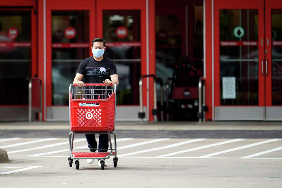 A shopper wears a mask as he pushes a shopping cart to his car Wednesday, March 18, 2020, in Houston. For most people, the coronavirus causes only mild or moderate symptoms, such as fever and cough. For some, especially older adults and people with existing health problems, it can cause more severe illness, including pneumonia.