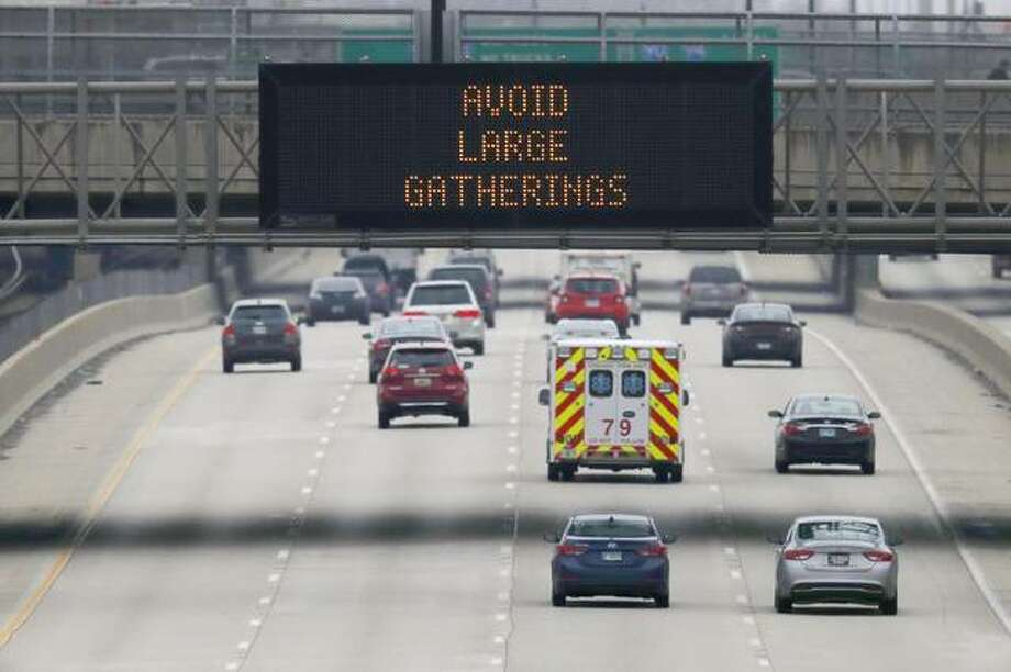 A public service announcement about coronavirus prevention is displayed on an electronic traffic message board as an ambulance travels northbound on Chicago's Dan Ryan Expressway, Thursday, March 19, 2020. (AP Photo/Charles Rex Arbogast)