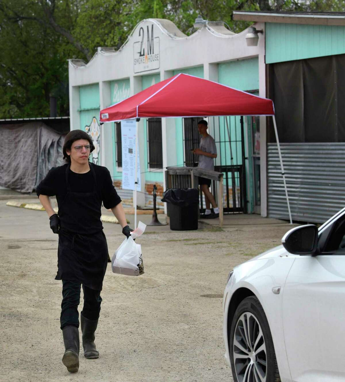 Nathaniel Campos rushes an order to a waiting customer at 2M Smokehouse. The acclaimed barbecue joint has now moved to a system where all of the food is sold to go with a makeshift drive-thru operation due to coronavirus precautionary measures.