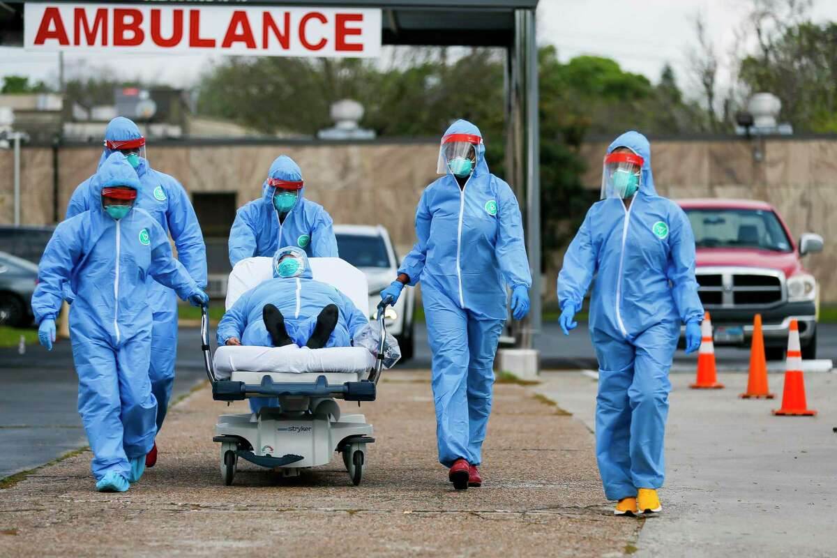 Medical personnel transport a patient from their car to an isolation area after the person displayed severe symptoms when they drove up in their car to be tested at the drive-thru testing center that opening, Thursday morning, March 19, 2020, at the United Memorial Medical Center in Houston.