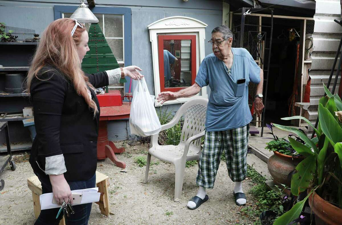 Forrest Myane, left, with Meals on Wheels San Antonio, delivers food to a man in March. The nonprofit is also helping in the vaccine effort.
