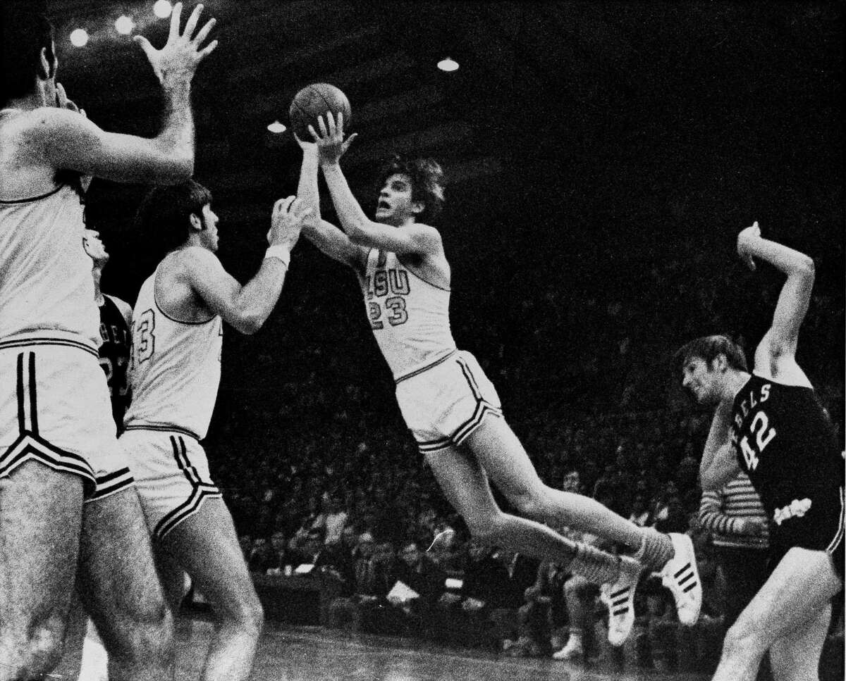 """Louisiana State Pete """"Pistol"""" Maravich (23) flies through the air during record breaking performance in Baton Rouge, Louisiana on February 1, 1970, to become college basketball's leading scorer of all-time. At right is University of Mississippi's Tom Butler (42) and at left are LSU's Danny Hester (35) and Bill Newton (43). (AP Photo)"""