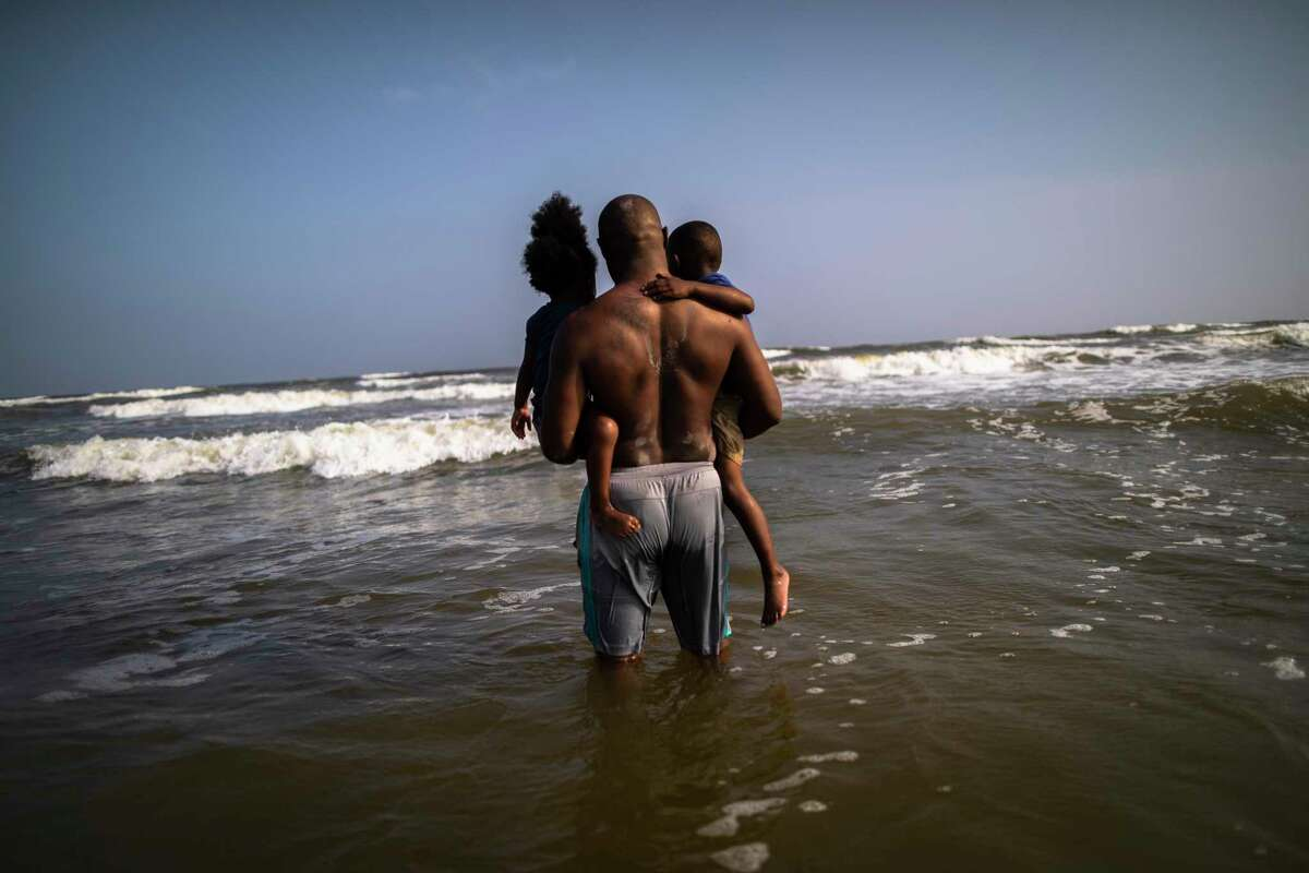Llewellyn Scott holds his children J'lyn Scott, 4, and Karolyn Scott, 3, showing them the water during a visit to Galveston Beach on Thursday, March 19, 2020.
