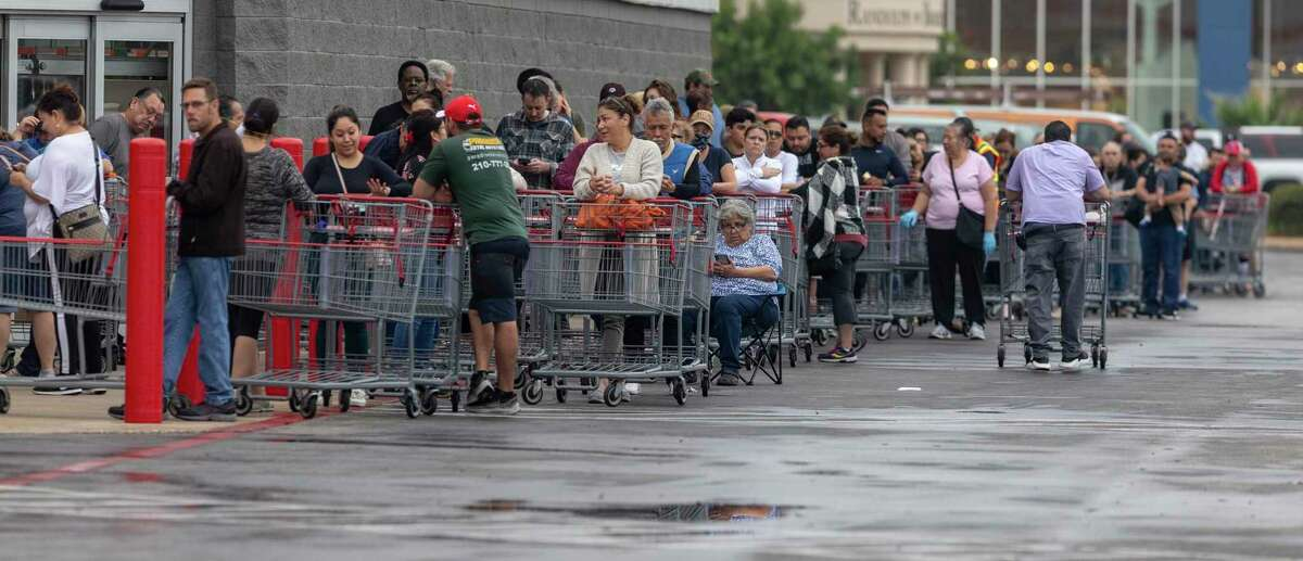 People line up outside the Costco store on UTSA Boulevard as they wait for it to open. Many area stores are still seeing runs on things like toilet paper and hand sanitizer as confirmed COVID-19 cases increase in Bexar County.
