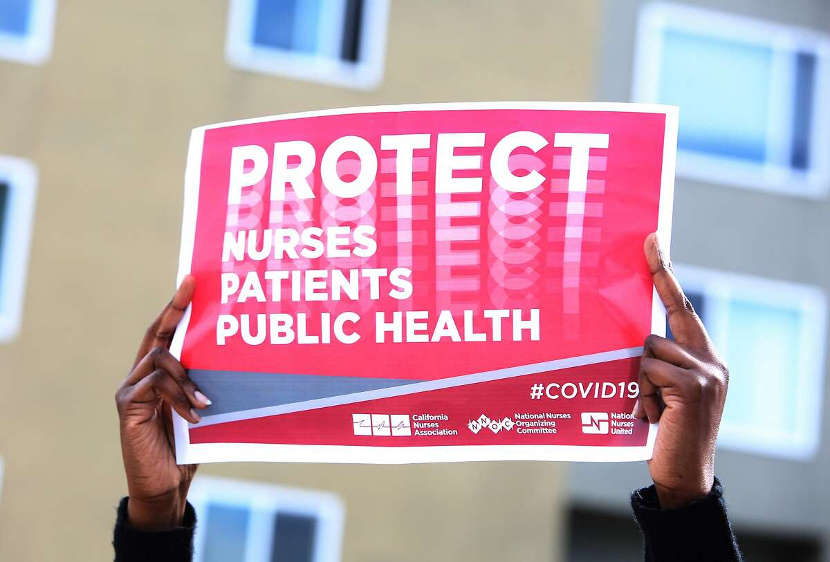 A protester holds a sign as she and others protest dangerously relaxed standards and having to reuse one-time use equipment during the coronavirus shutdown outside Kaiser Permanente San Francisco Medical Center on Thursday, March 19, 2020 in San Francisco, Calif.
