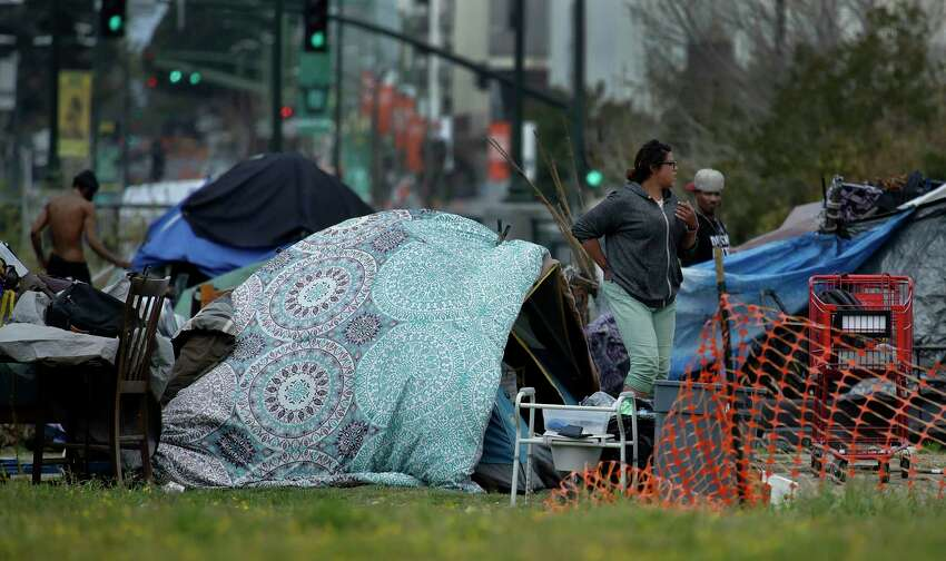 People are seen in a homeless encampment on Thursday, March 19, 2020, in Oakland, Calif. California Gov. Gavin Newsom has authorized $150 million in emergency funding to protect homeless people in California from the spread of COVID-19. $100 million will go to local governments for shelter support and emergency housing, while the remaining $50 million will be for purchasing travel trailers and lease rooms in hotels, motels and other facilities to provide places for the homeless to self-isolate. (AP Photo/Ben Margot)