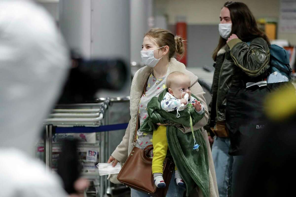 A passengers wearing face mask with her baby walks to medical experts to be checked after arriving from a foreign country at Sheremetyevo airport outside Moscow, Russia, Thursday, March 19, 2020. Authorities in Russia are taking vast measures to prevent the spread of the disease in the country. The measures include closing the border for all foreigners, shutting down schools for three weeks, sweeping testing and urging people to stay home. For most people, the new coronavirus causes only mild or moderate symptoms. For some it can cause more severe illness. (AP Photo/Pavel Golovkin)