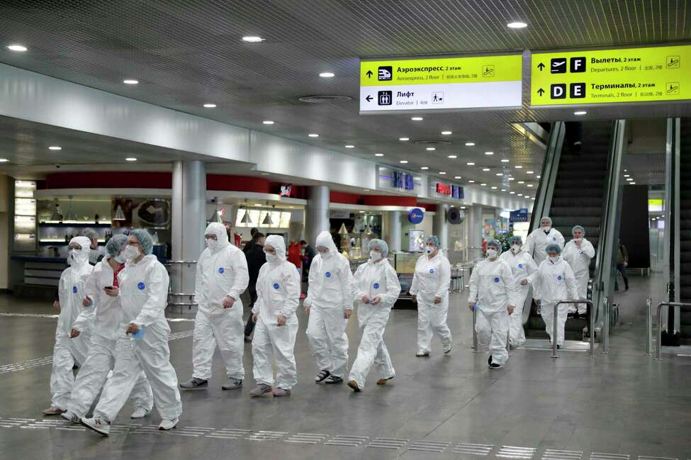 Russian medical experts walk to start their shift to check passengers arriving from foreign countries at Sheremetyevo airport outside Moscow, Russia, Thursday, March 19, 2020. Authorities in Russia are taking vast measures to prevent the spread of the COVID-19 virus in the country. The measures include closing the border for all foreigners, shutting down schools for three weeks, sweeping testing and urging people to stay home. For most people, the new coronavirus causes only mild or moderate symptoms. For some it can cause more severe illness. (AP Photo/Pavel Golovkin)