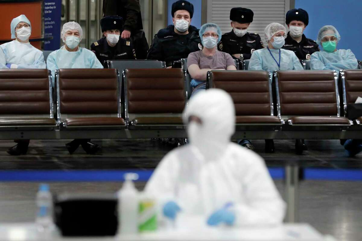 Russian medical experts and police officers take a pause as they wait to check passengers arriving from foreign countries at Sheremetyevo airport outside Moscow, Russia, Thursday, March 19, 2020. Authorities in Russia are taking vast measures to prevent the spread of the disease in the country. The measures include closing the border for all foreigners, shutting down schools for three weeks, sweeping testing and urging people to stay home. For most people, the new coronavirus causes only mild or moderate symptoms. For some it can cause more severe illness. (AP Photo/Pavel Golovkin)